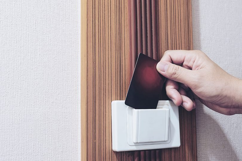 Man putting key card switch in hotel room